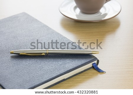 Pen put on a book and coffee cup on wood table background - stock photo