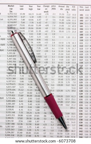 Pen resting on stock market financial data in a newspaper