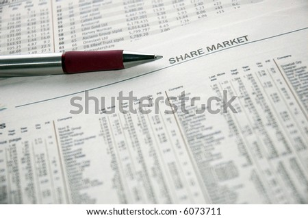Pen resting on stock market financial data in a newspaper - stock photo