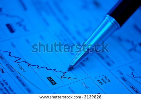Pen showing diagram on financial report/magazine (blue tone) - stock photo