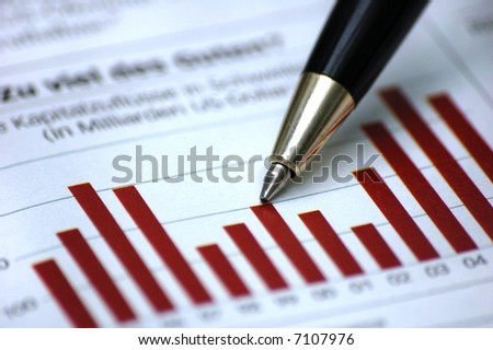 Pen showing diagram on financial report/magazine (light) - stock photo