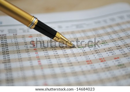 Pen showing figures on financial report/magazine