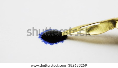 Pen tip in a drop of ink - stock photo