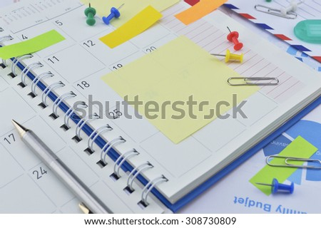 Pen with colorful post It notes and pin on business diary page - stock photo