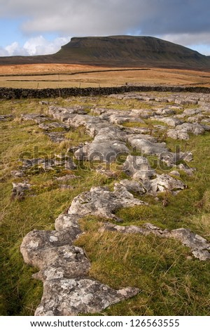 Pen-y-Ghent in Yorkshire Dales National Park viewed across limestone rocks - stock photo
