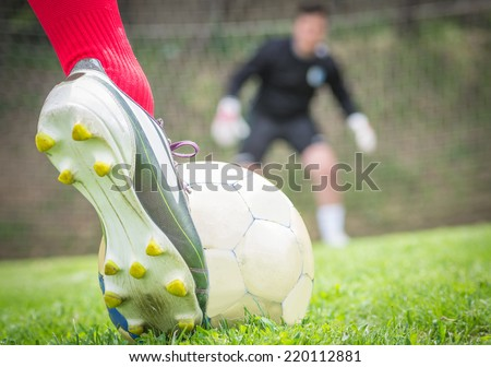 penalty kick. A soccer player is ready to hit the ball. Goalkeeper is gonna dive on the left - stock photo