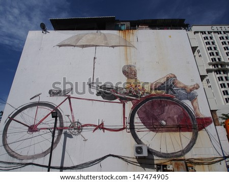 PENANG, MALAYSIA- APRIL 19:Street Mural tittle 'The Awaiting Trishaw Paddler' Painted by Ernest Zacharevic on April 19, 2013. It was painted in conjunction with the 2012 George Town Festival.  - stock photo