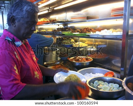 PENANG, MALAYSIA-APRIL 13:Unidentified worker prepares 'nasi kandar' or 'kandar rice' in Penang, Malaysia on April 13, 2012. Nasi kandar is a popular spicy dish originating from Penang Indian Muslim