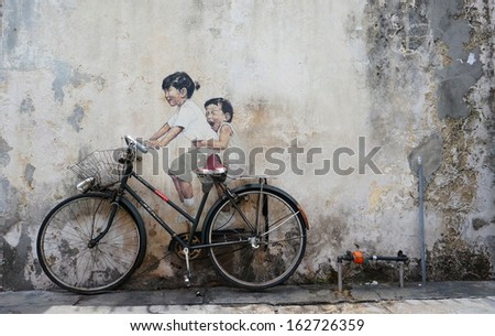 PENANG, MALAYSIA-AUG 13: A mural 'Little children on a bicycle painted by Ernest Zacharevic in Penang on Aug.13, 2013. Thisl is one of the 9 murals painted by him in early 2012.  - stock photo