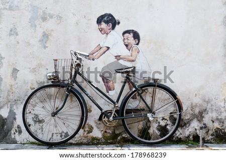PENANG, MALAYSIA - AUGUST 16: Street Mural Installation Painting tittle 'Little Children on a Bicycle' painted by Ernest Zacharevic in Penang on August 16, 2013. - stock photo