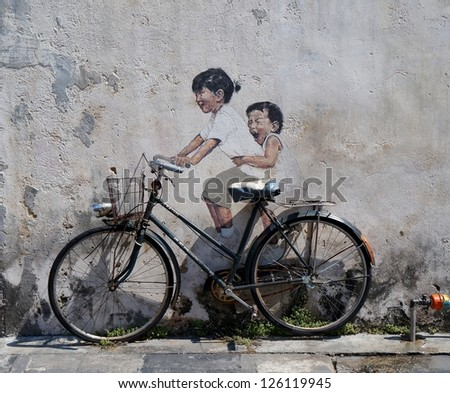 PENANG, MALAYSIA-DEC.9: Street Mural entitled 'LIttle Children on a Bicycle' painted by Ernest Zacharevic in Penang on Dec.9, 2012. It was painted in conjunction with the 2012 George Town Festival. - stock photo