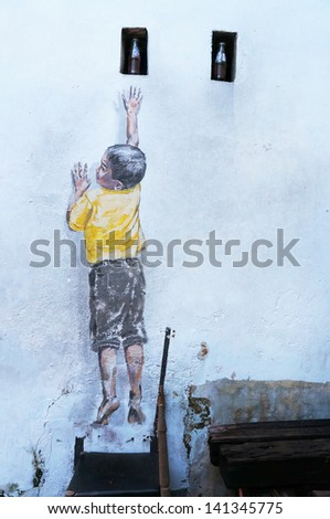 PENANG, MALAYSIA-DEC.9: Street Mural entitled 'Reaching Up' painted by Ernest Zacharevic in Penang on Dec.9, 2012. It was painted in conjunction with the 2012 George Town Festival. - stock photo
