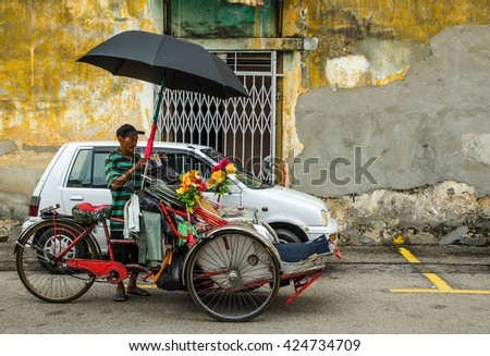 PENANG, MALAYSIA-30 DECEMBER 2011: unidentified man standing beside his trishaw. iconic traditional transportation in Penang, Malaysia.
