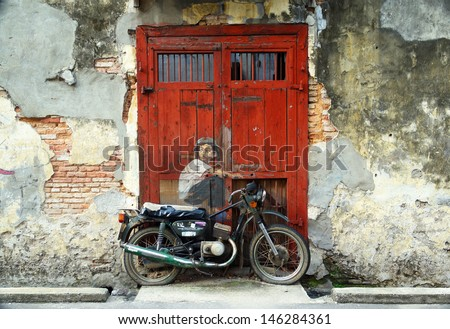 PENANG, MALAYSIA-JULY 6: General view of a mural 'Boy on a Bike' painted by Ernest Zacharevic in Penang on July 6, 2013. The mural is one of the 9 murals paintings in early 2012.  - stock photo