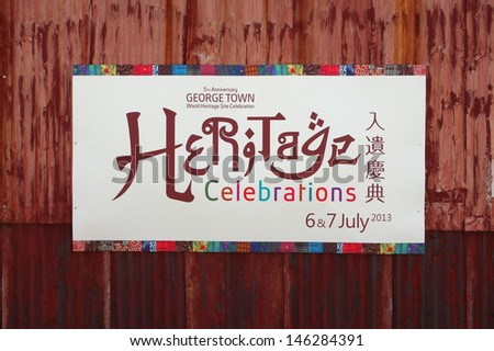PENANG, MALAYSIA-JULY 6: Official poster of the 5th Anniversary George Town World Site Heritage Celebrations posted on wall during the World Heritage Site Celebration in Penang on July 6, 2013. - stock photo