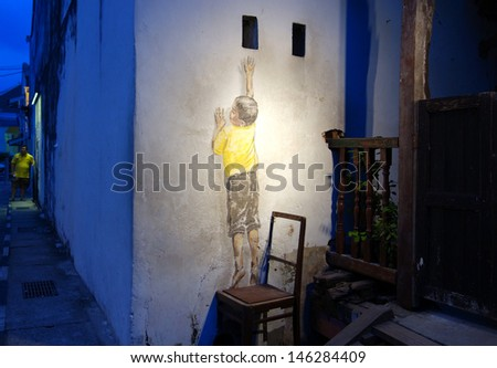 PENANG, MALAYSIA-JULY 6: Street Mural entitled 'Reaching Up' painted by Ernest Zacharevic in Penang on July 6, 2013. It was painted in conjunction with the 2012 George Town Festival.  - stock photo