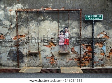 PENANG, MALAYSIA-JULY 6: Street Mural tittle 'Children on the Swing' painted by Louis Gan in Penang on July 6, 2013. It was painted in conjunction with the 2012 George Town Festival.  - stock photo