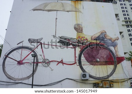 PENANG, MALAYSIA- JULY 6: Street Mural tittle 'The Awaiting Trishaw Paddler' painted by Ernest Zacharevic in Penang on July 6, 2013. It was painted in conjunction with the 2012 George Town Festival. - stock photo