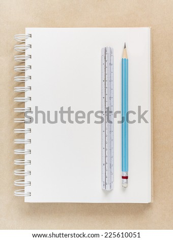 Pencil and blank notebook on vintage paper background. - stock photo