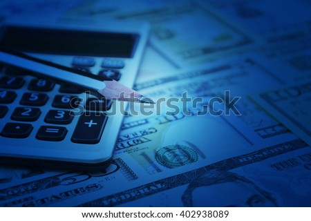 Pencil and calculator on dollar bank note money, Blue tone, Finance concept