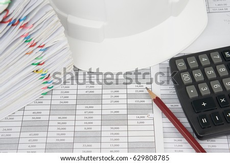 Pencil and calculator on finance account have blur white engineer hat and pile overload document of report and receipt with colorful paperclip as background. Industrial successful concept photography.