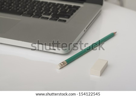 pencil and eraser next to laptop in the office - stock photo
