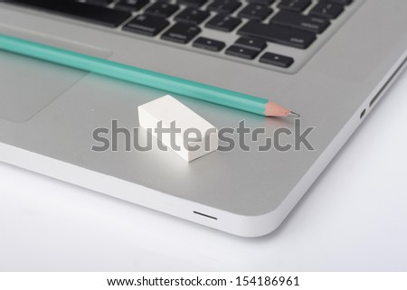 pencil and eraser on a laptop in the office - stock photo