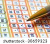 Pencil and lottery ticket closeup with marked numbers. - stock photo