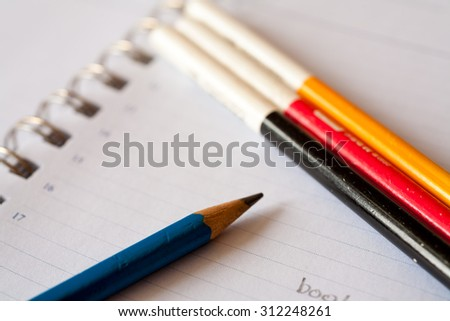 pencil and notebook with space for text or image, selective focus