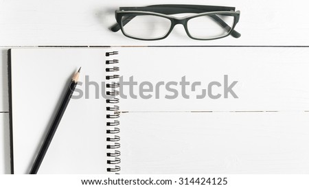 pencil and notepad with eyeglasses over white table view from above