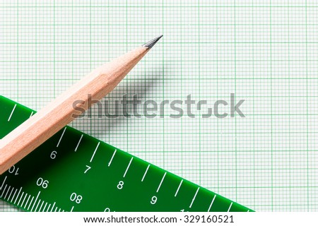 Pencil and Ruler on green graph paper with copy space - stock photo