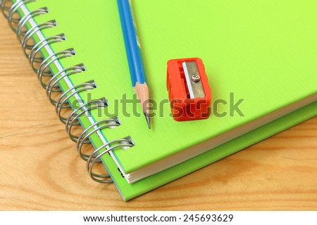Pencil and sharpener put on a notebook. - stock photo