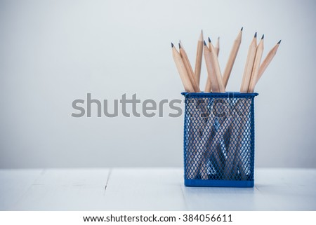pencil box on white wooden table - stock photo