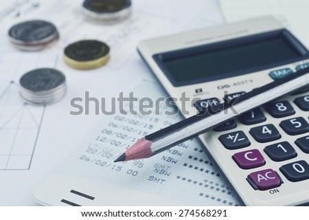 Pencil, calculator, coin and saving book on graph paper, saving concept - stock photo