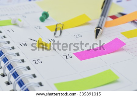 Pencil, colorful sticky notes and pin on business diary page - stock photo