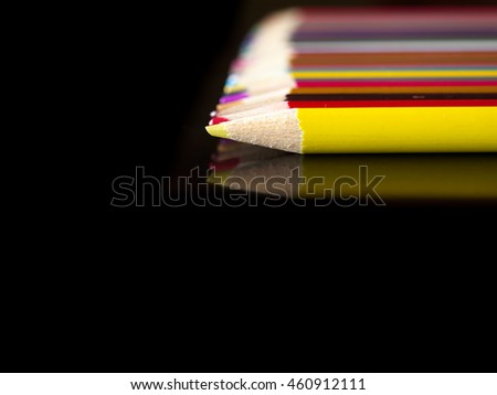 Pencil crayons lying in a line on a dark colored table.