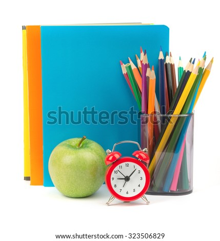 Pencil cup with crayons, alarm clock and apple on copybooks on isolated white background