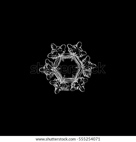 Pencil drawing: white snowflake on black background. This sketch based on macro photo of real snow crystal: with big, flat hexagonal center and short, broad arms.