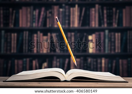 Pencil floating on the heavy books