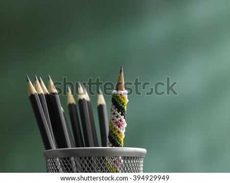 pencil in front of blackboard ,concept  stand out from the crowd - stock photo