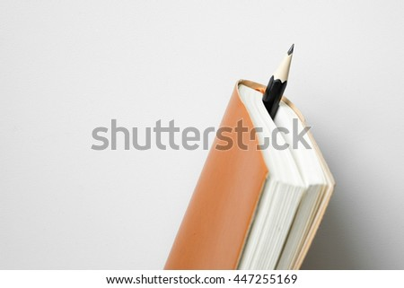 Pencil insert between leather diary on white desk - stock photo