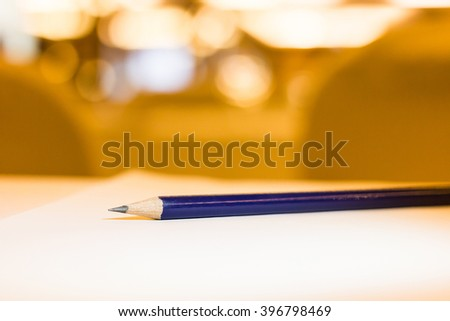 Pencil lay on a table in a hotel conference room.(on warm white light)