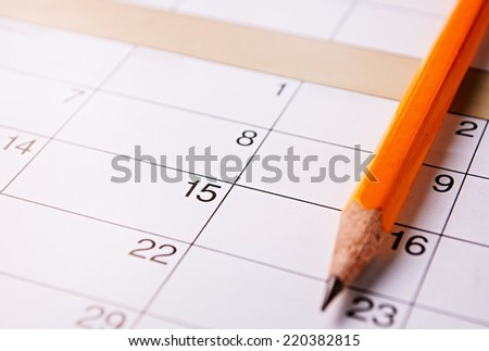 Pencil lying on a calendar with blank squares and dates conceptual of schedules, reminders and organization - stock photo