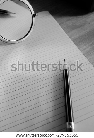 pencil lying on blank paper with black and white tone