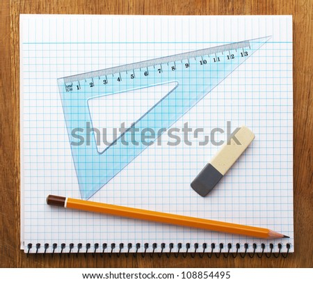 pencil notebook and eraser on wooden desk - stock photo