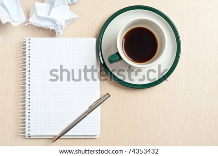 Pencil on a white notepad with cup of coffee on desk - stock photo