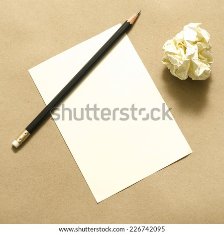Pencil on clear white paper with crumble paper balls on brown color background - stock photo