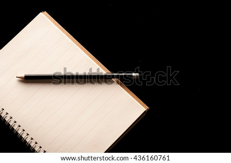 Pencil on Notebook use in business office black background - stock photo