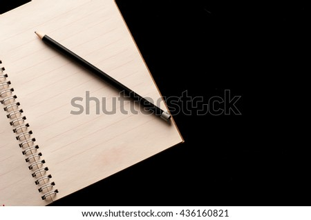 Pencil on Notebook with use in business office black background - stock photo