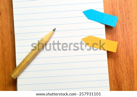 Pencil on open note book. Colorful Sticky paper arrows - stock photo